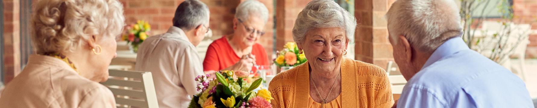 Three Beacon Hill senior living community residents sitting outside enjoying a meal