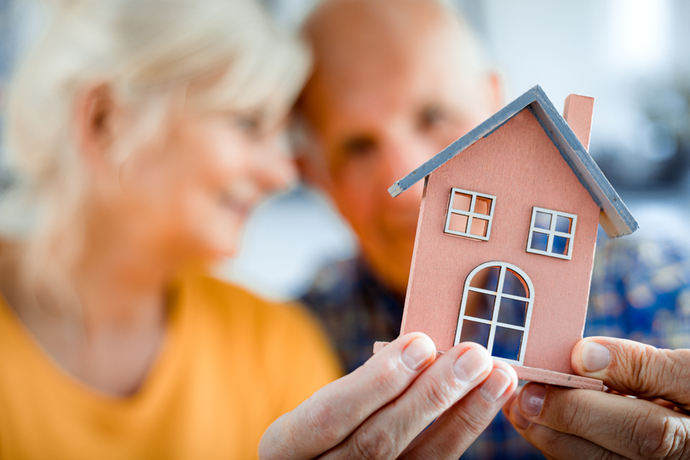 Two seniors holding small model of a house