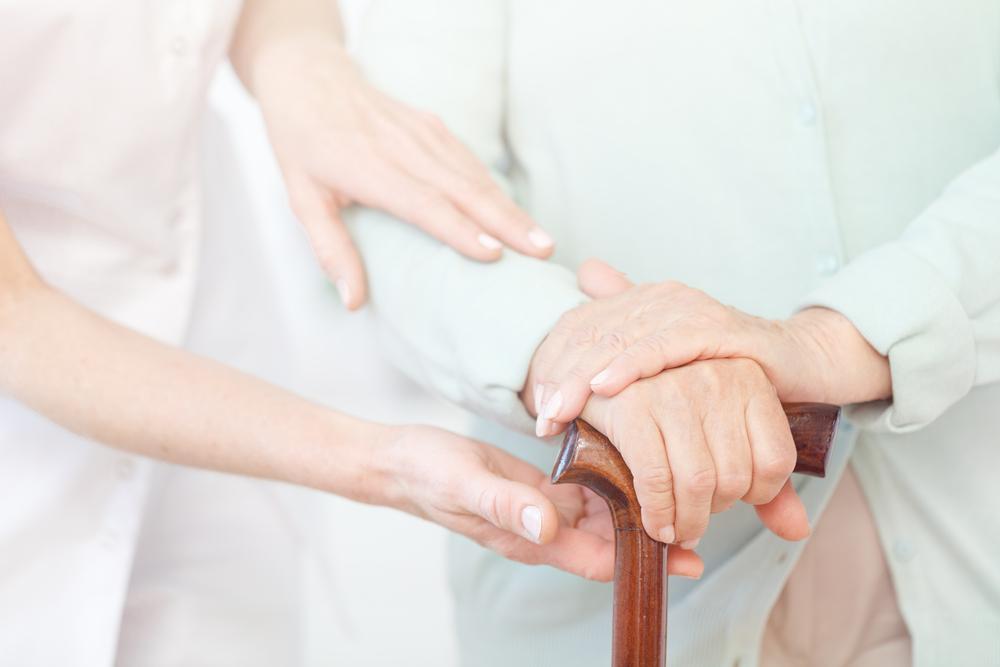 Nursing helping senior woman with a cane