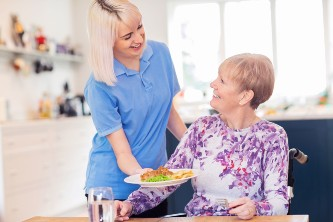 senior living worker bringing a senior a meal