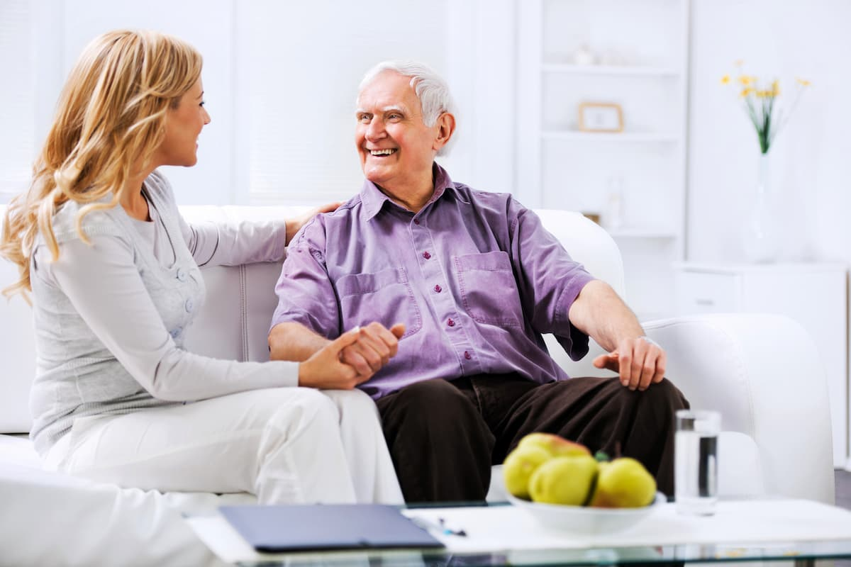 Female caregiver sitting on the couch and holding hands with older man.