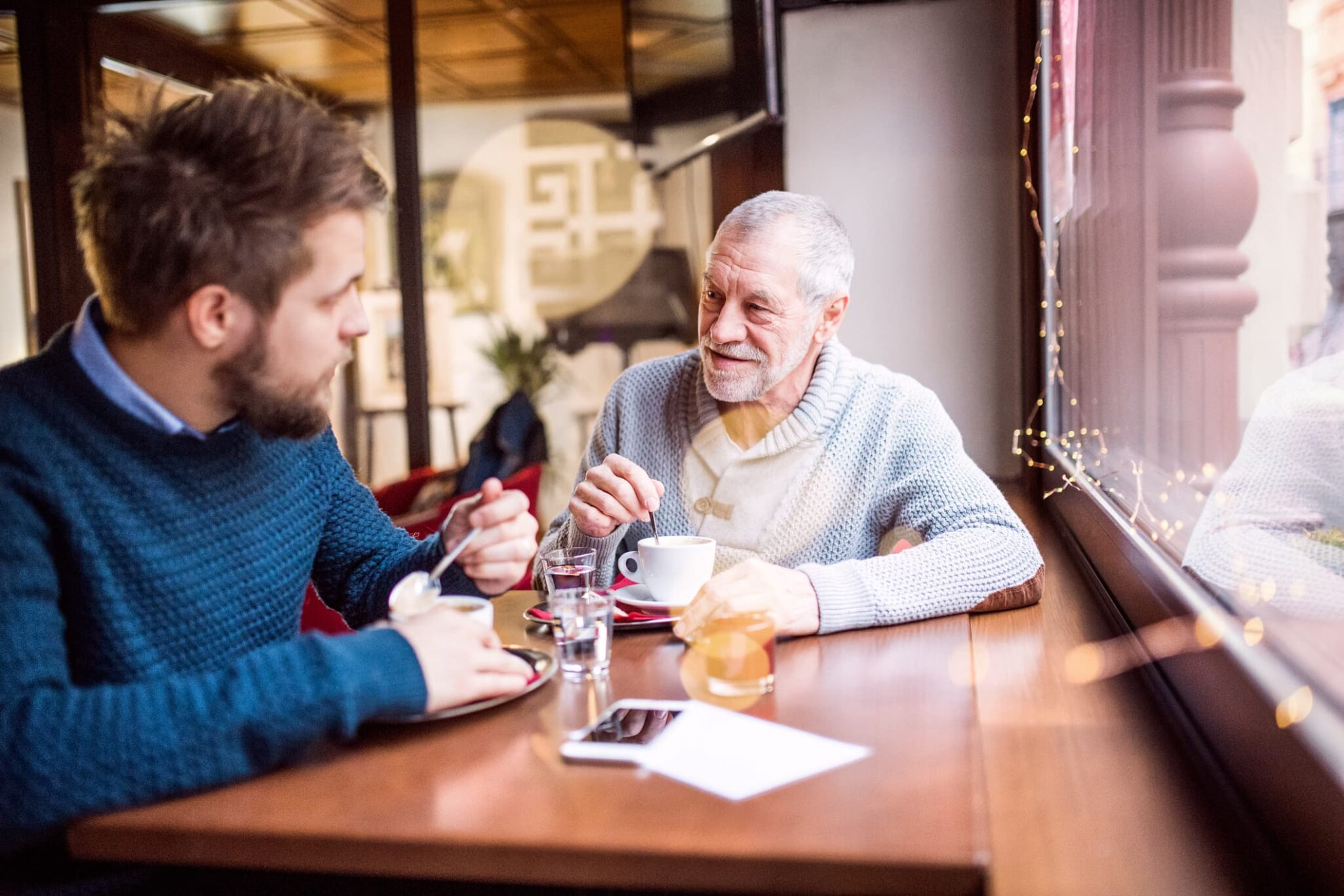 Adult son chatting over coffee with senior father