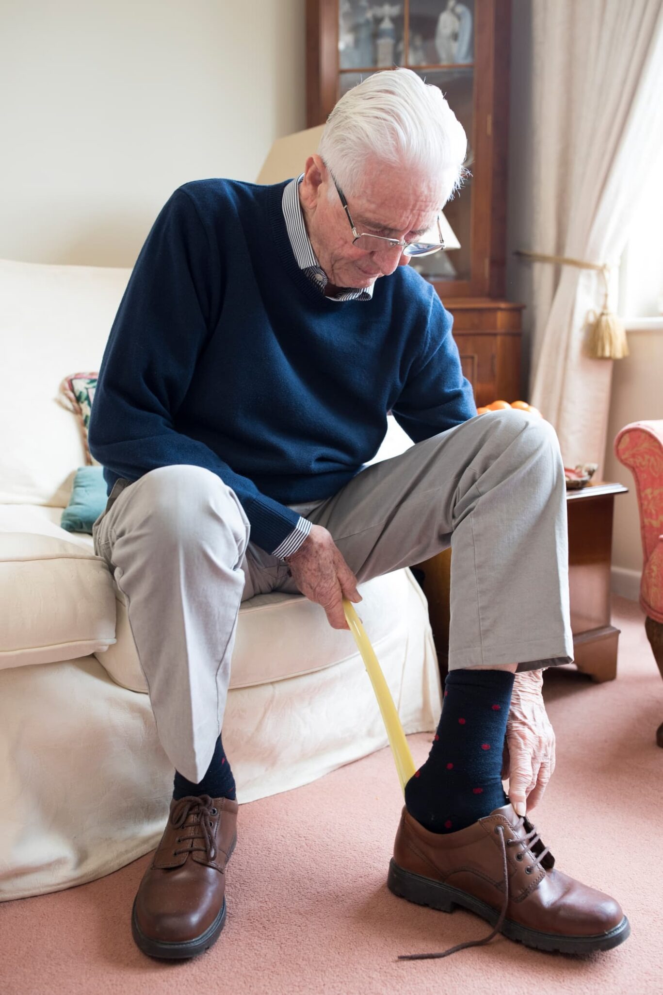An older man sits on a couch and uses a long-handled shoe-horn to aid in putting on shoes.