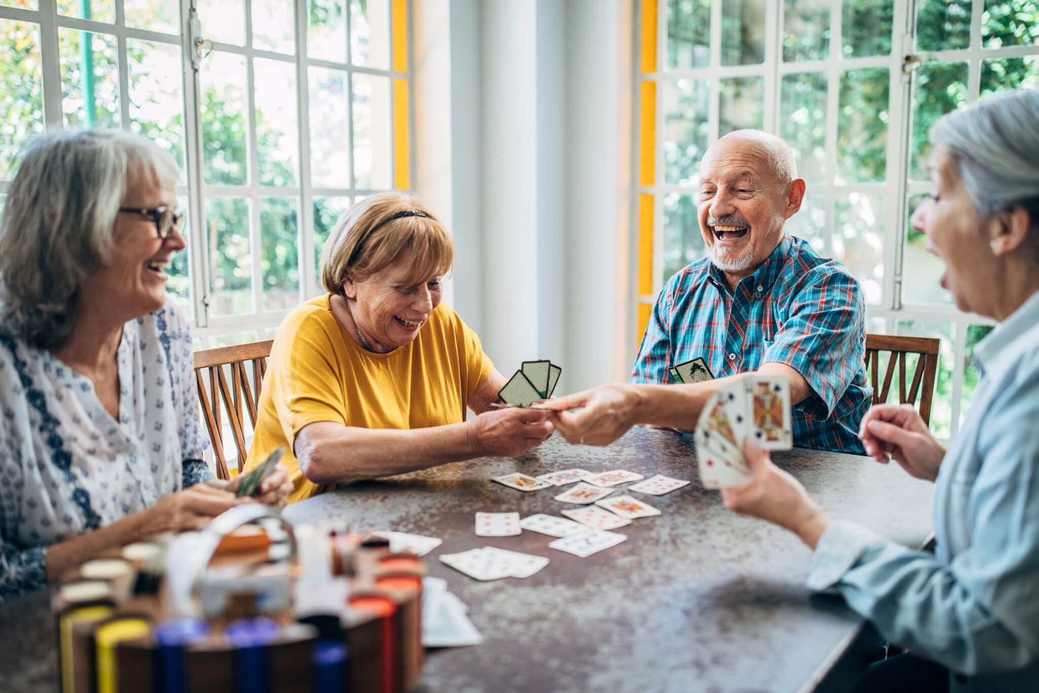 Group of older adults sitting around a table and having fun playing cards.