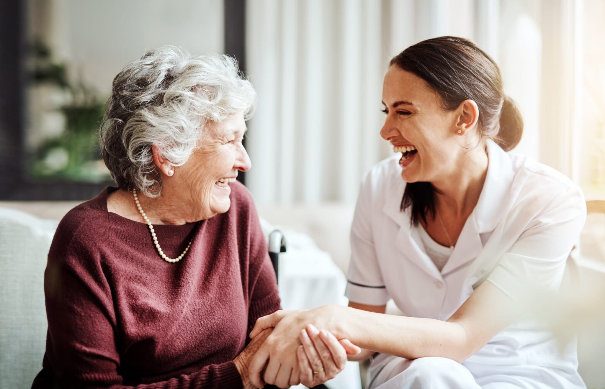 Older woman sitting on couch and smiling with her female caregiver.